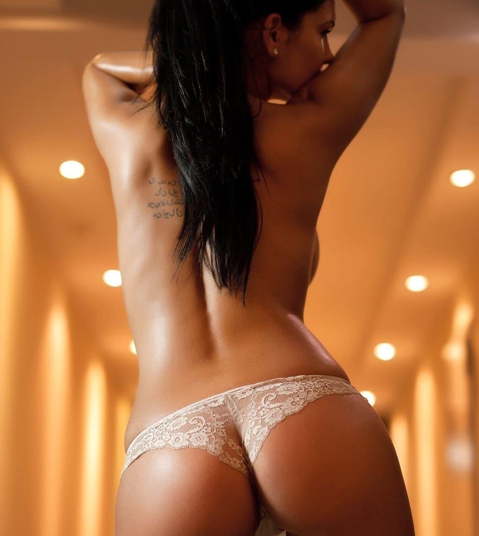 девушка брюнетка волосы со спины в ажурных трусиках стоит подняв руки на голову