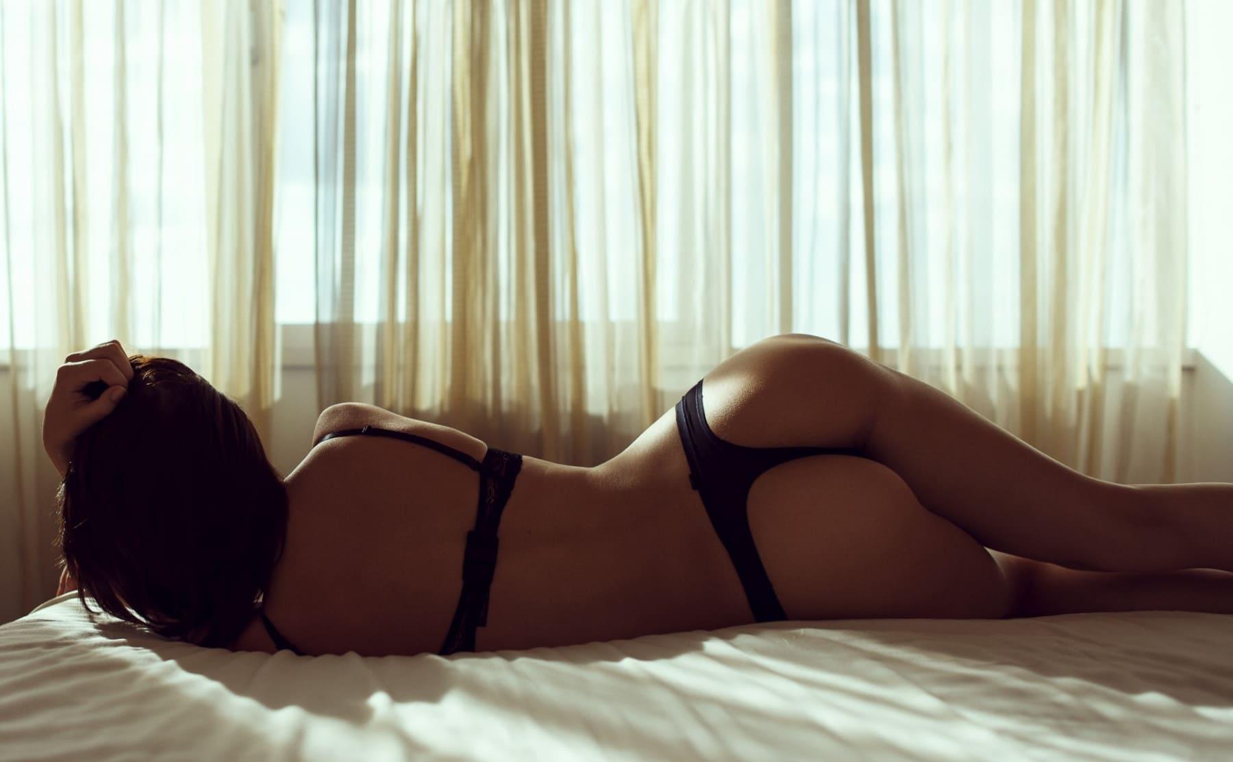 девушка со спины брюнетка без лица лежит на животе на кровати у окна в черном сексуальном белье