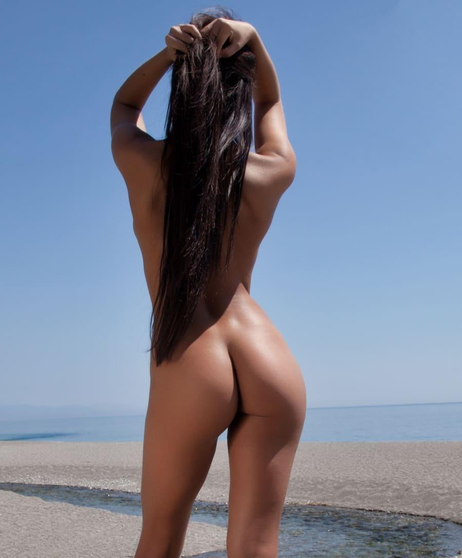 фото девушки брюнетки со спины голая стоит на пляже у моря