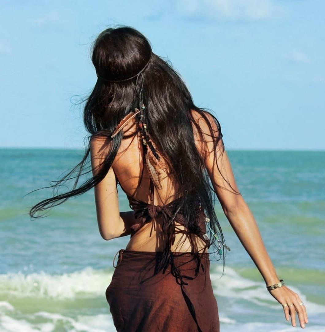 девушка брюнетка волосы со спины на берегу моря стоит