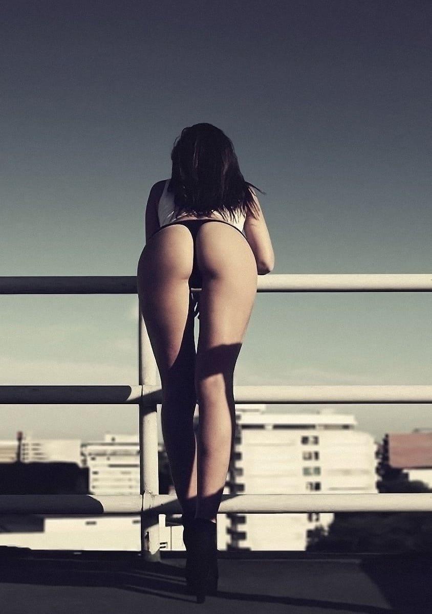 фото девушки брюнетки со спины стоит голая на крыше облакотившись на ограждение в стрингах