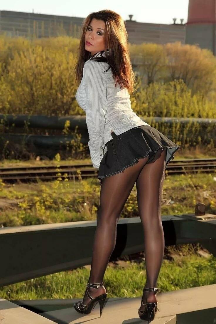 девушки в мини юбках и колготках стоит на каблуках в поле возле железнодорожных путей в босоножках на каблуках и белой кофте с длинными рукавами
