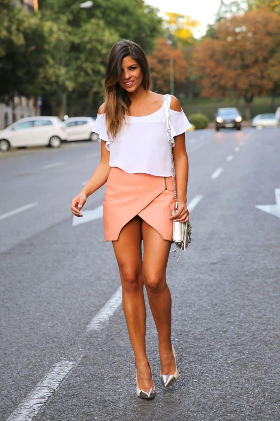 красивые девушки в мини юбках на каблуках идет по дороге улыбается в левой руке держит маленький ридикюль