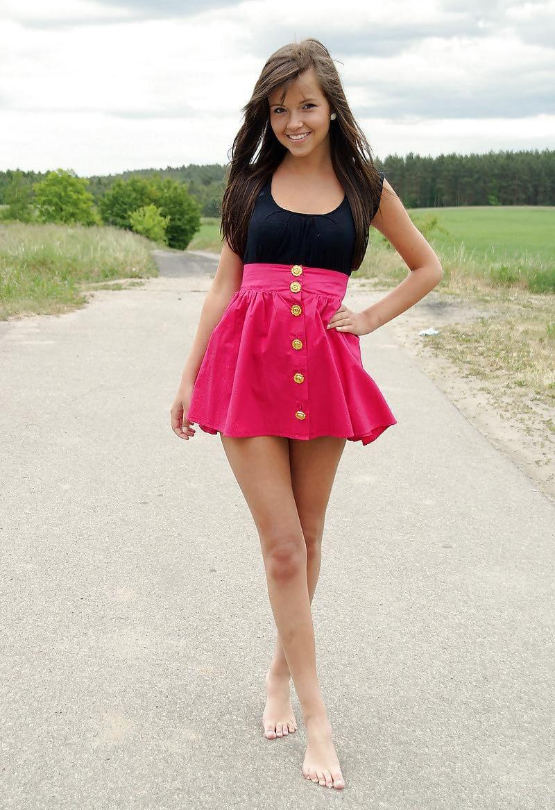 Красивая русская молодая девушка с длинным русым волосом в розовой мини юбке и черном топике стоит босая на дороге улыбаясь