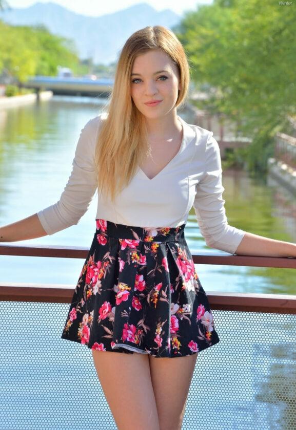 Фото красивой девушки блондинки сдлинным волосом в цветастой мини юбке стоит на мостике у реки в белой кофточке опираясь на перила улыбаясь