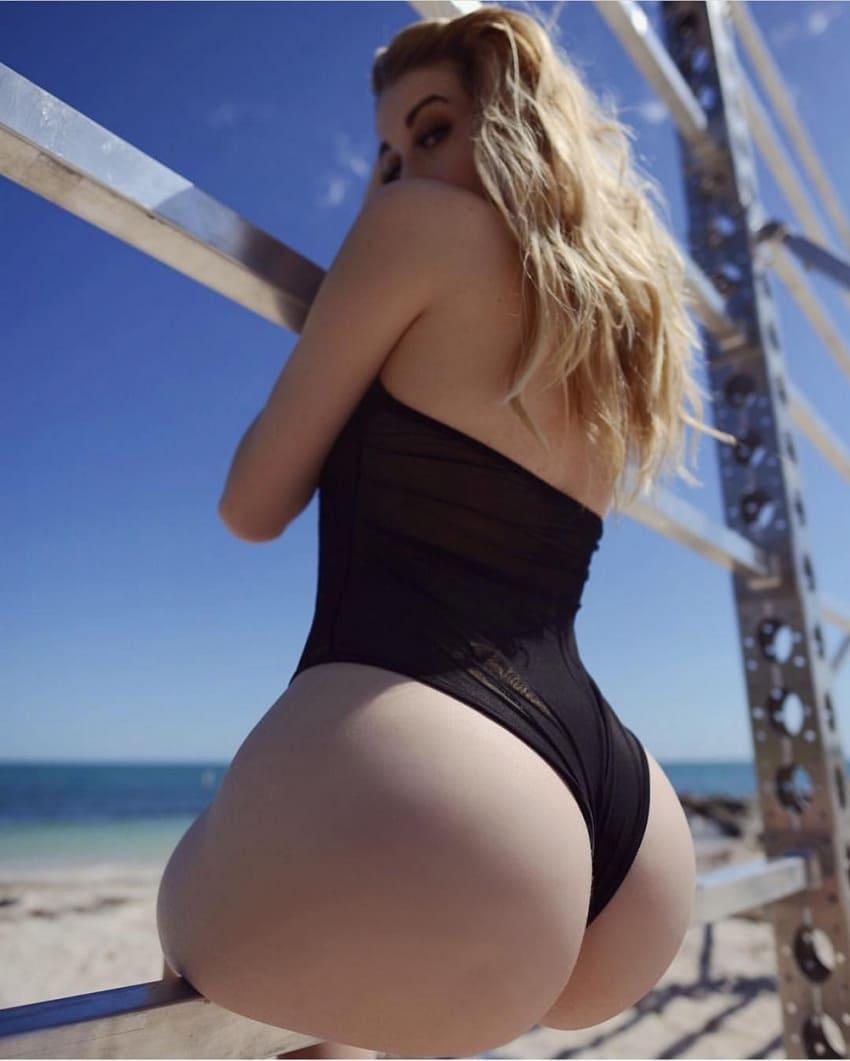 красивые девушки с большой попой блондинка в черном сплошном купальнике сидит на деревянной палке