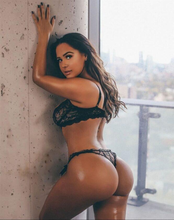 красивые девушки с большой попой у стены стоит в черном прозрачном сексуальном нижнем белье, руки подняла на стену, вся блестит от масла, длинные волосы распущены