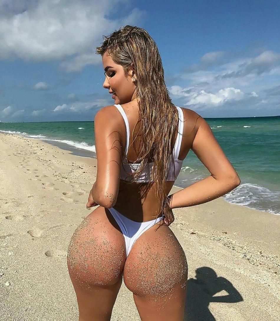 красивые девушки с большой попой блондинка с длинным мокрым распущенным волосом стоит на пляже на берегу океана в белом купальнике