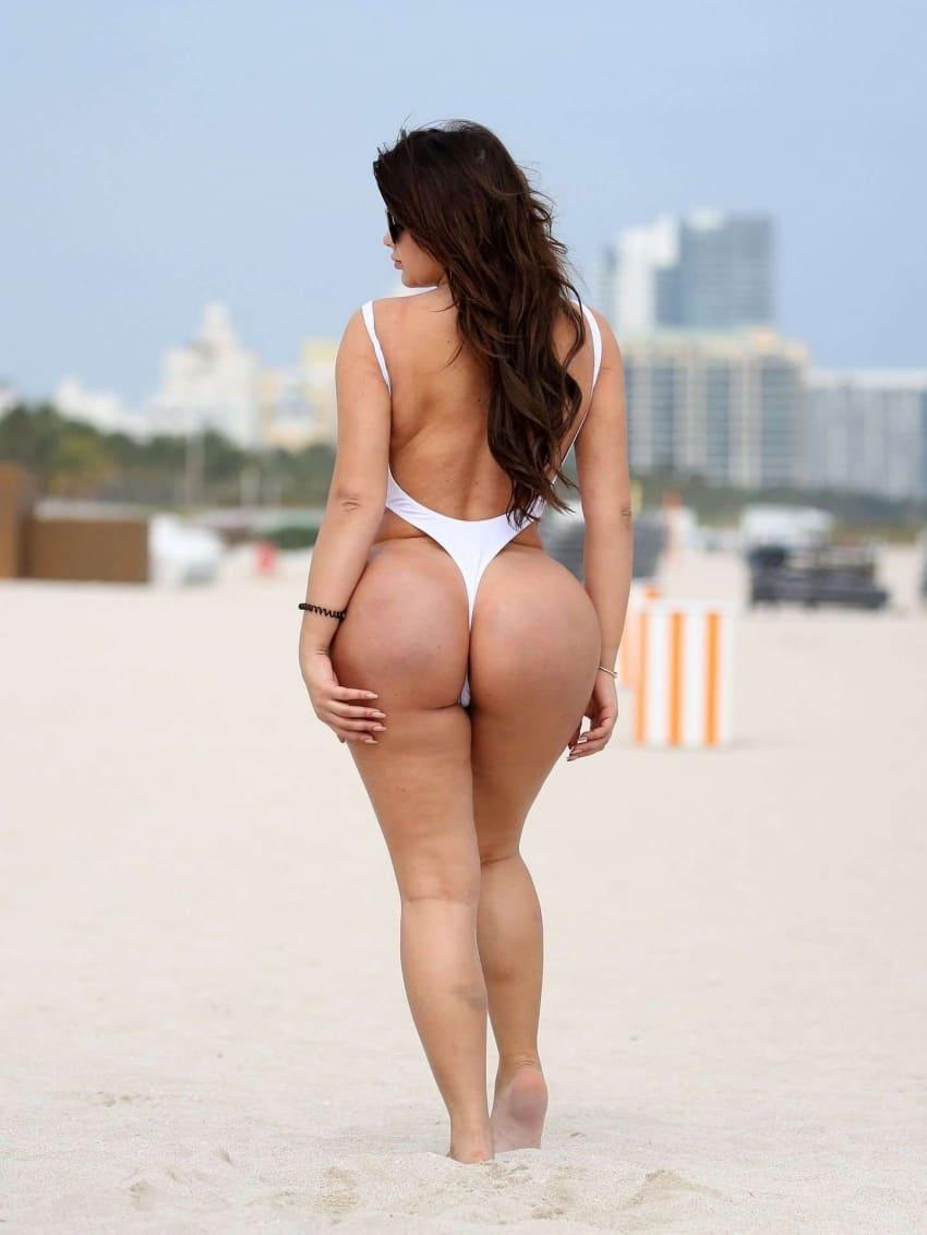 красивые девушки с большой попой и пухлыми ножками на пляже в белом сплошном купальнике стоит, длинные темно каштановые волосы по поясницу