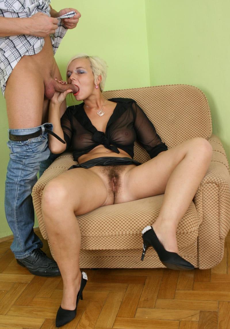 порно фото зрелых волосатых дам блондинка с короткой стрижкой сидит в кресле широко раздвинула ноги в черных туфлях, делает минет