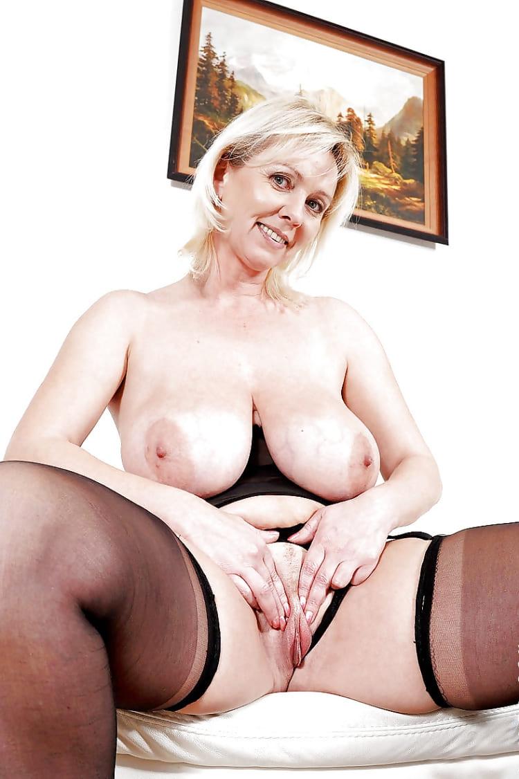 порно фото зрелых дам блондинка с большими сиськами в кресле сидит в черных чулках, раздвинула ноги ласкает свою пилотку