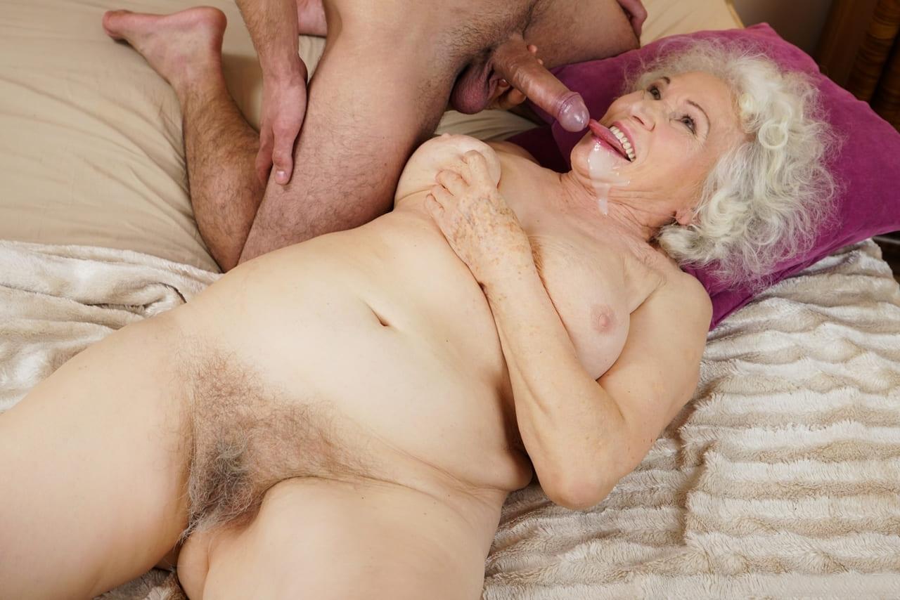 порно фото зрелых дам блондинка с волосатой пиздой лежит на спине на кровати языком облизывает пенис который обкончал ей лицо