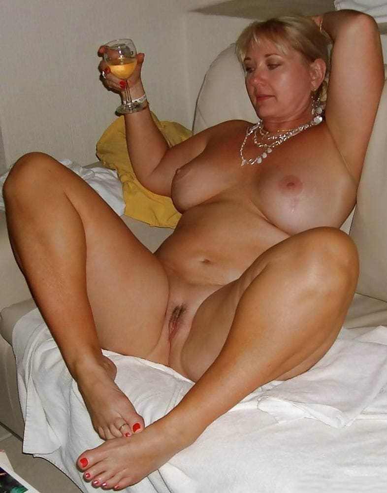 порно фото зрелых дам русское в теле с большими сиськами голая в кресле сидит раздвинув ноги с бокалом в руке, на шее бусики несколько нитей, яркий педикюр