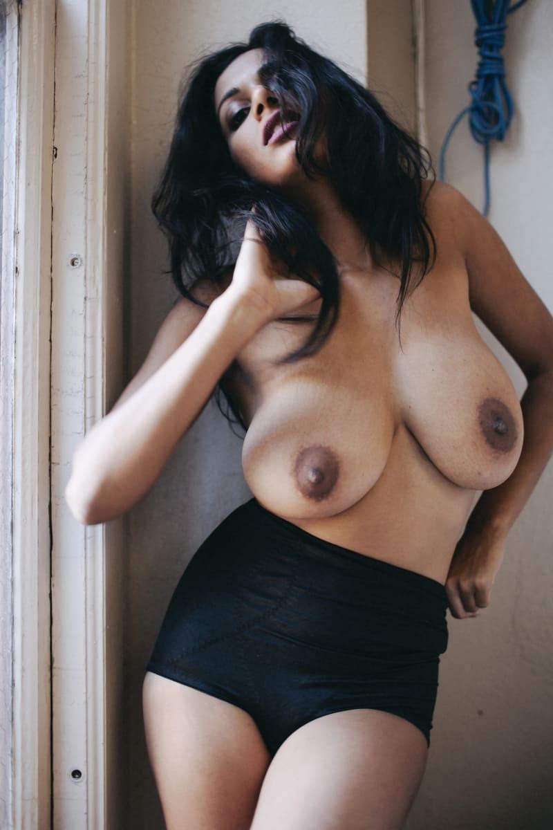 Голая арабка с большими сиськами в черных высоких трусах стоит