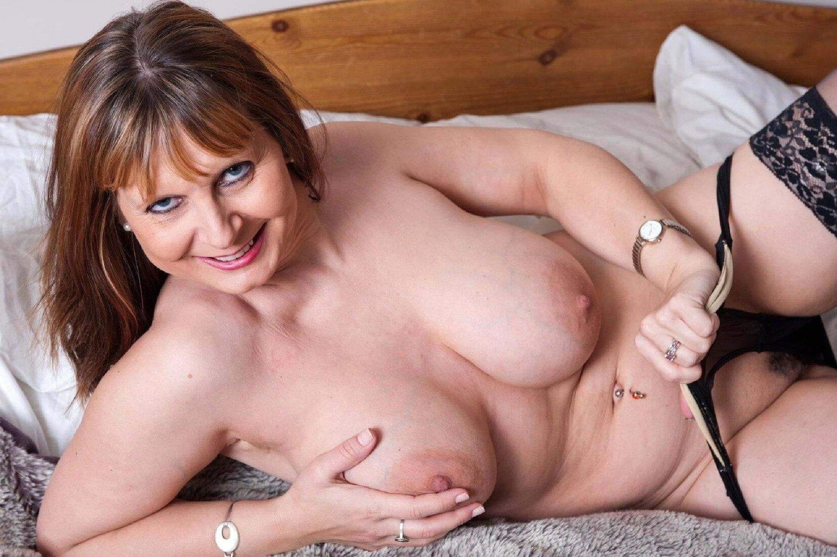 большие сиськи зрелых теток фото красивой женщины лежащей в кровати в черных чулках и рукой отягивающей трусики, в пупке пирсинг.
