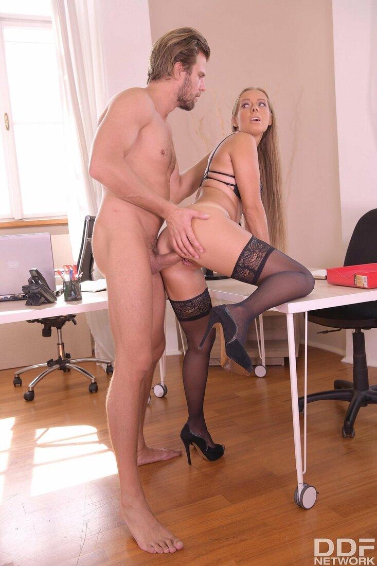 Порно трахает секретаршу фото длинноволосая секретарша голая в черных чулках стоит задом оперевшись правой ногой на стол в кабинете и начальник ебет её в пизду подойдя сзади.