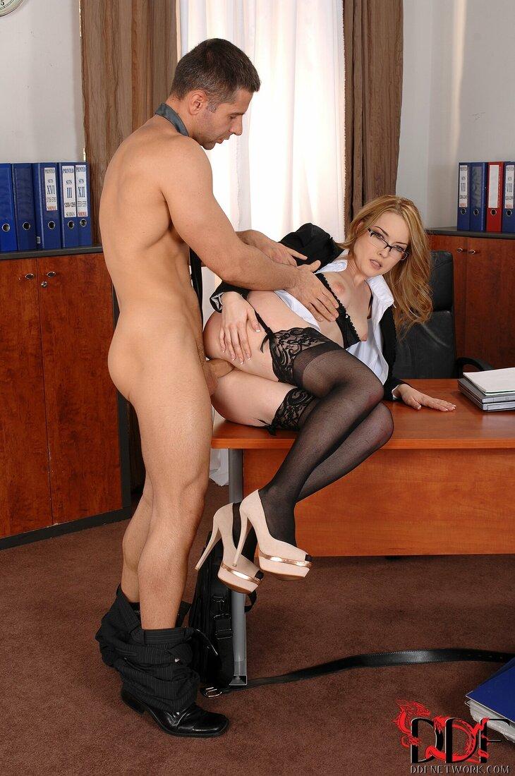 Порно трахает секретаршу фото блондинка в черных чулках и туфлях на каблуке лежит на левом боку на столе в кабинете начальника, расстегнув блузку видны сиськи за которые он её лапает засунув хуй в пизду, на глаза у шлюхи очки, волосы распущены.