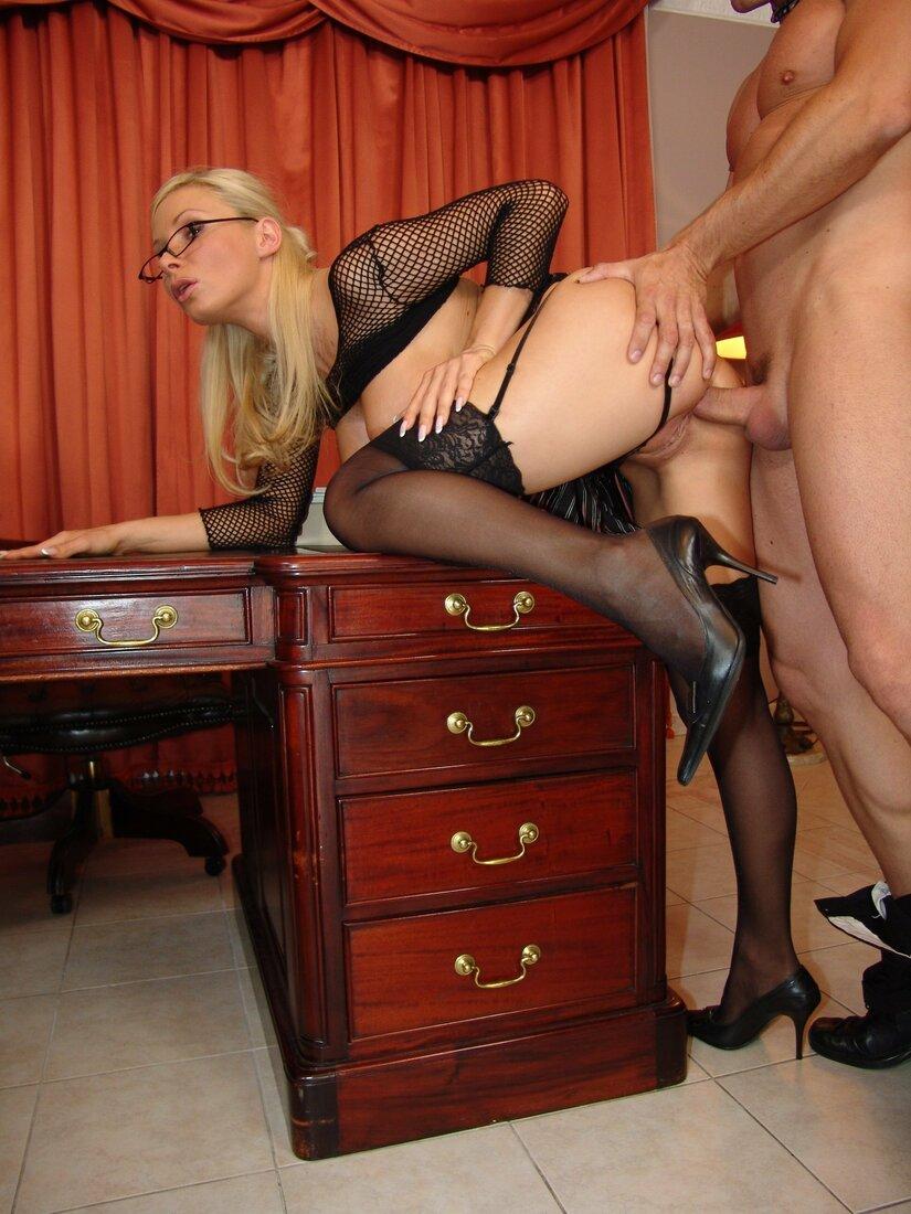 Порно трахает секретаршу фото блондинки в очках, черных чулках на поясе, и блузке в виде сетки которая стоит в кабинете начальника раком задрав правую ногу на стол из дерева, босс подошел сзади и ебет её в жопу.