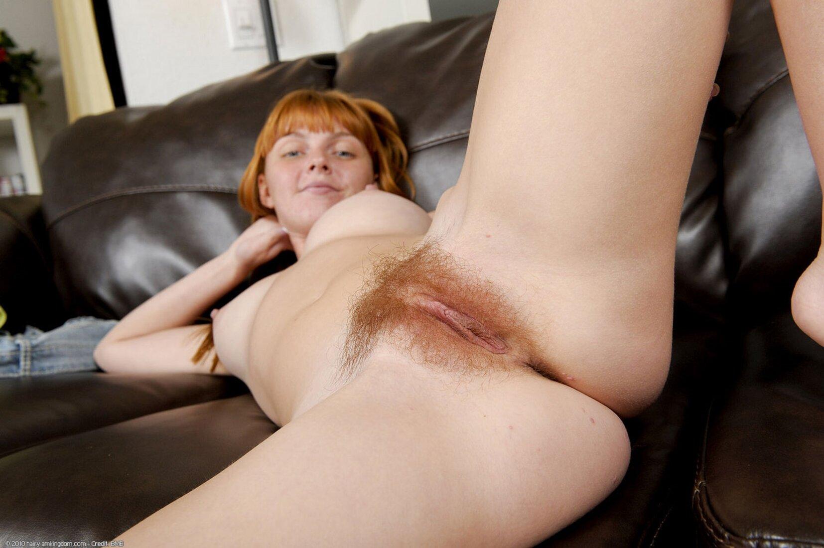 рыжая волосатая пизда девушка лежит на черном кожаном диване раздвинув ноги, классные сиськи стоят торчком.
