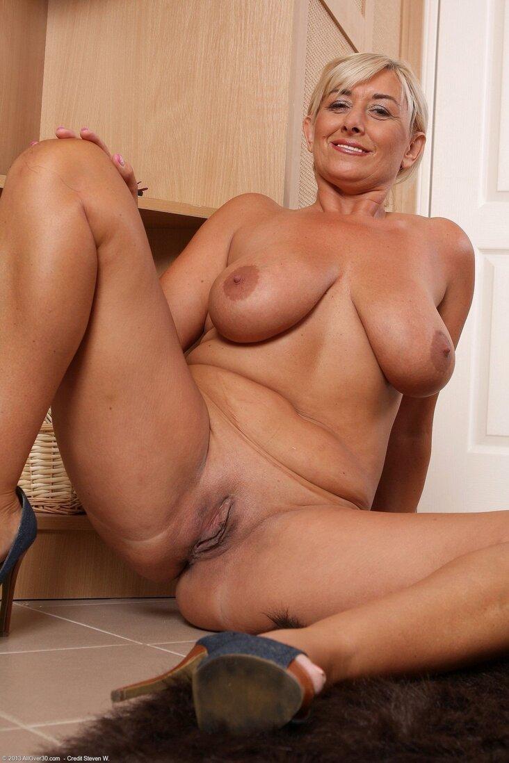 Тетки за 40 голая женщина с большими сиськами сидит на полу в туфлях на каблуке раздвинув ноги показывая бритую пизду.
