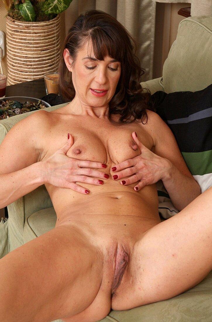 Красивая голая тетка за 40 полулежит сжимая сиськи раздвинув ноги.