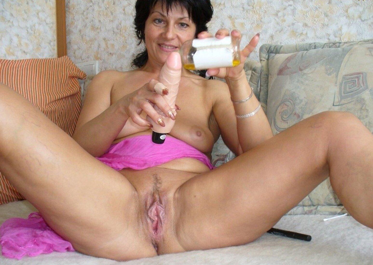 Тетки за 40 женщина смазывает вибратор лежа на кровати и раздвинув ноги улыбается.