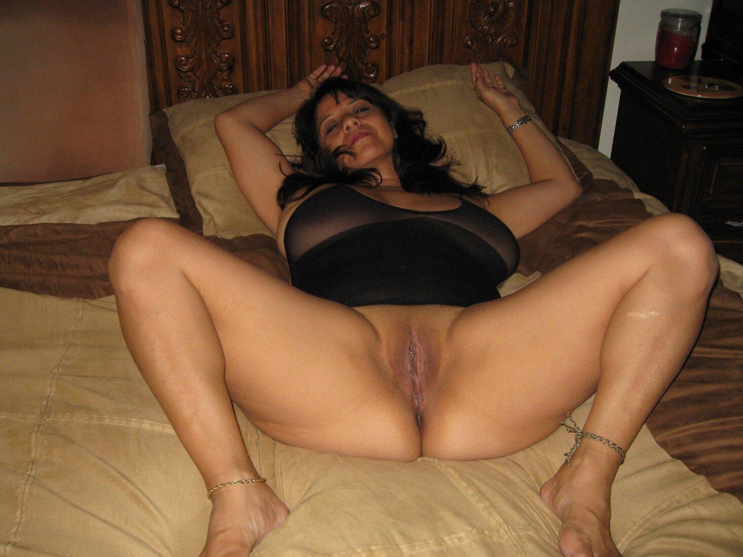 Тетки за 40 лежит на кровати раздвинув ноги и показывает пизду.