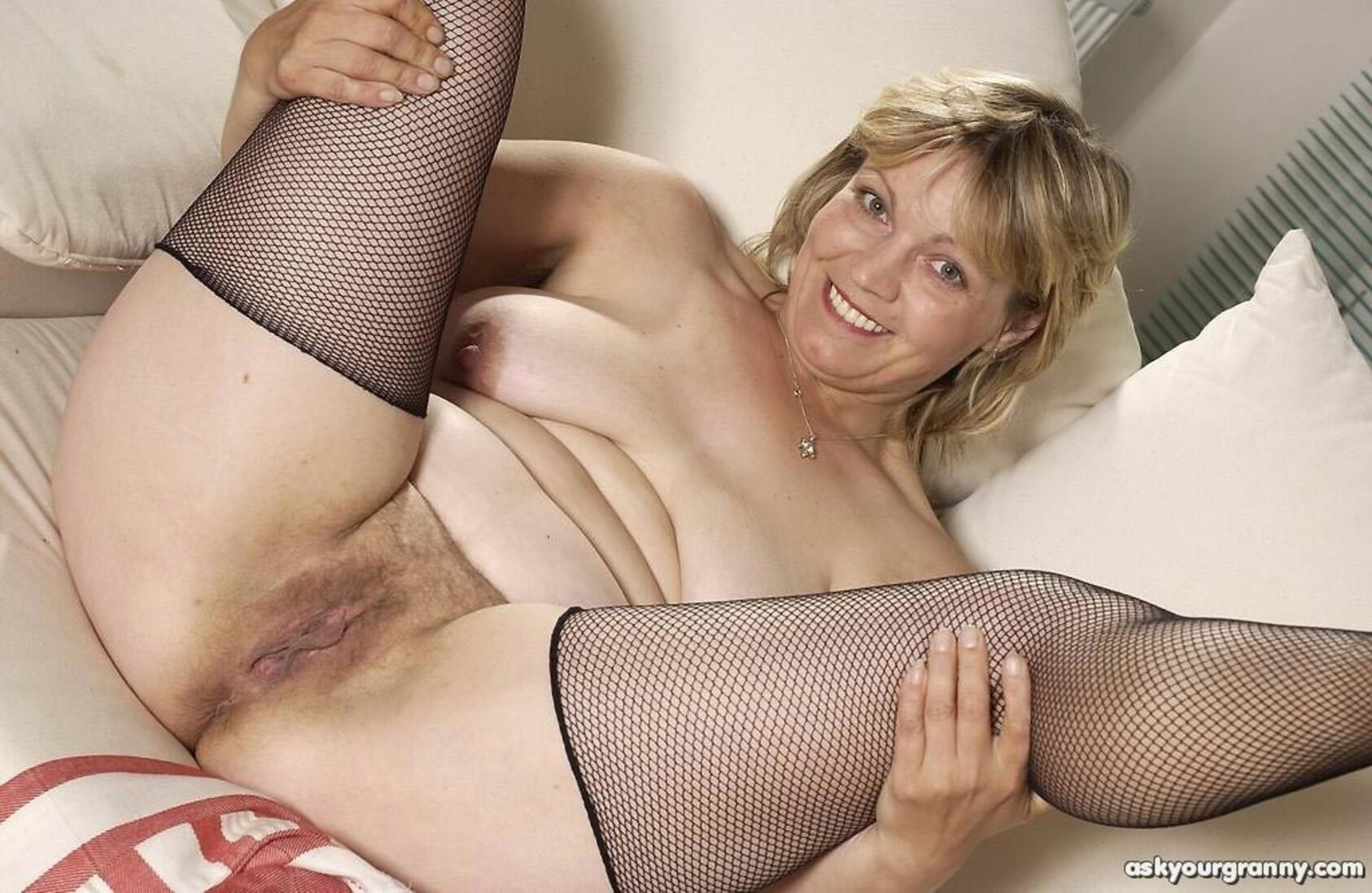Тетки за 40 лежит на кровати задрав и раздвинув ноги в черных сетчатых чулках.