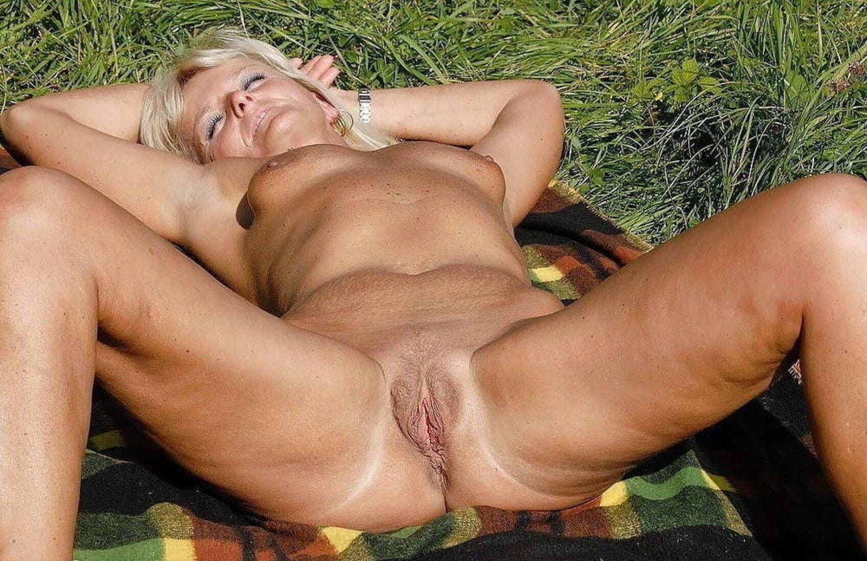 Тетки за 40 блондинка лежит на траве.