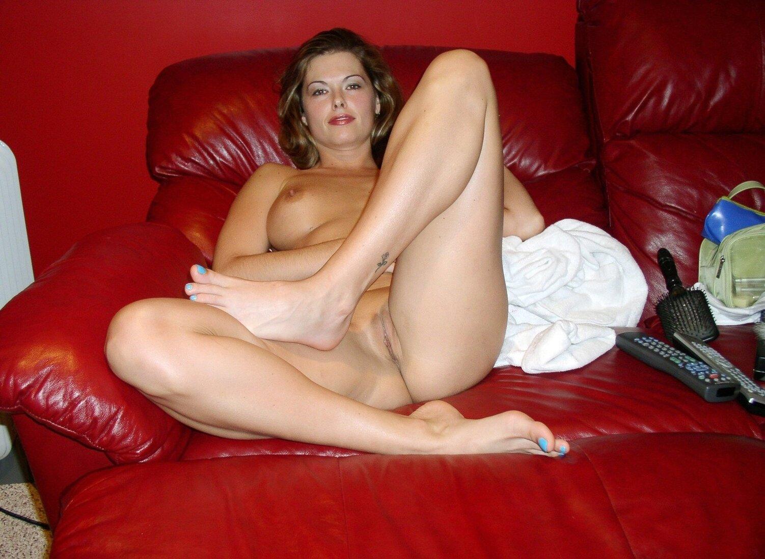 Тетки за 40 очень красивая женщина лежит на красном кожаном диване, показывая свои прелести.