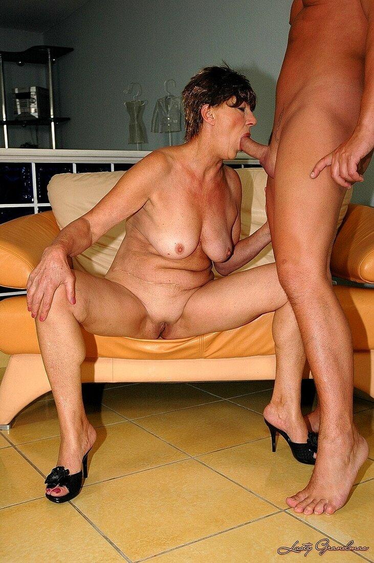 Порно со зрелыми женщинами фото голая брюнетка со стройной фигурой в черных туфлях на каблуке сидит на кушетке широко раздвинув ноги и сосет хуй наслаждаясь минетом, пизда волосатая, стрижка короткая.