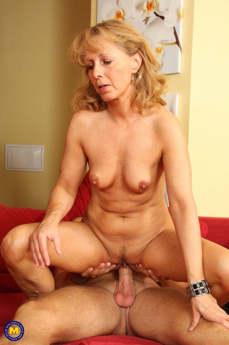 Порно со зрелыми женщинами фото симпотичной блондинки которую ебут на красном диване, она сидит голая на члене раздвинув ноги лицом к камере, сиськи средние торчат, пизда с интимной стрижкой, глаза прикрыты, рот слегка приоткрыт, левой рукой опирается на ногу мужика сидящего снизу, правую руку положила себе на правой бедро.