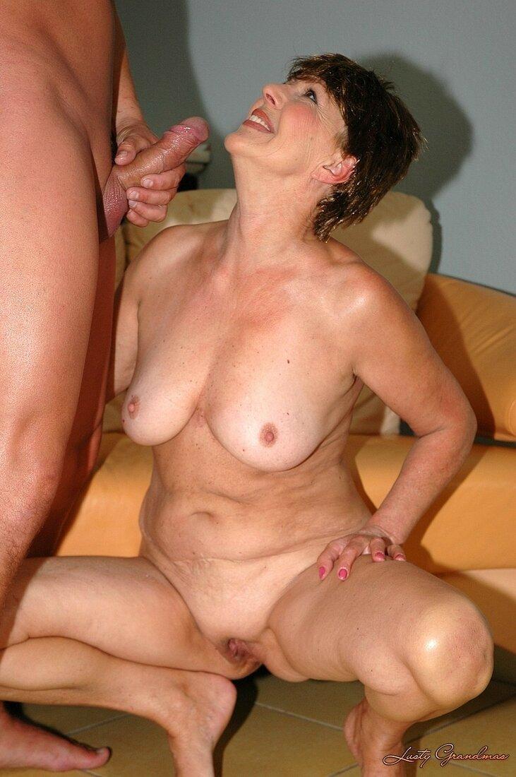 Порно со зрелыми женщинами фото брюнетки сидящей на корточках перед мужиком держащем свой хуй перед её лицом, сиськи торчат, ноги раздвинуты, видна небритая пизда, глаза озорные голова поднята широко и задорно улбыается.