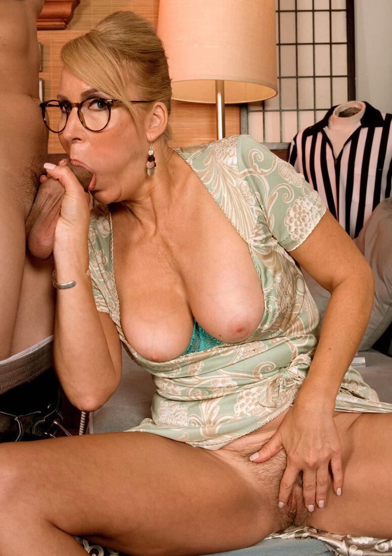 Порно со зрелыми женщинами фото красивой шлюшки с большими голыми сиськами в очках, она сидит на диване и взявшись правой рукой за хуй сосет его, левой рукой раздвигает пизду с интимной стрижкой.
