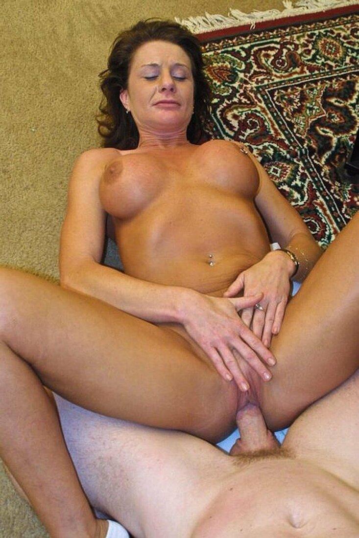 Порно со зрелыми женщинами фото красивая брюнетка с классной грудью лежит на полу с ковром и её ебет мужик в пизду, голова приподнята, глаза прикрыты, руками ласкает клитор.