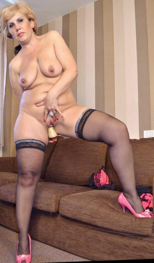 Порно со зрелыми женщинами фото голая блондинка стоит в розовых туфлях на каблуке и черных чулках, одну ногу поставила на диван, сиськи торчат, левой рукой раздвигает пизду, правой снизу запихивает во влагалище вибратор.